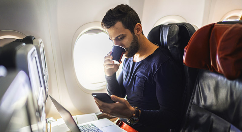 Man Drinking Coffee on Plane